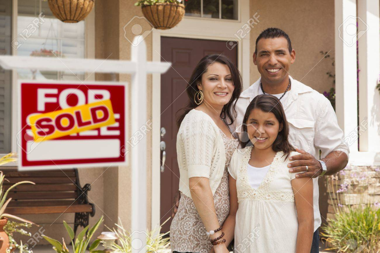 Hispanic Mother, Father and Daughter in Front of Their New Home with Sold Home For Sale Real Estate Sign. Stock Photo - 14203869