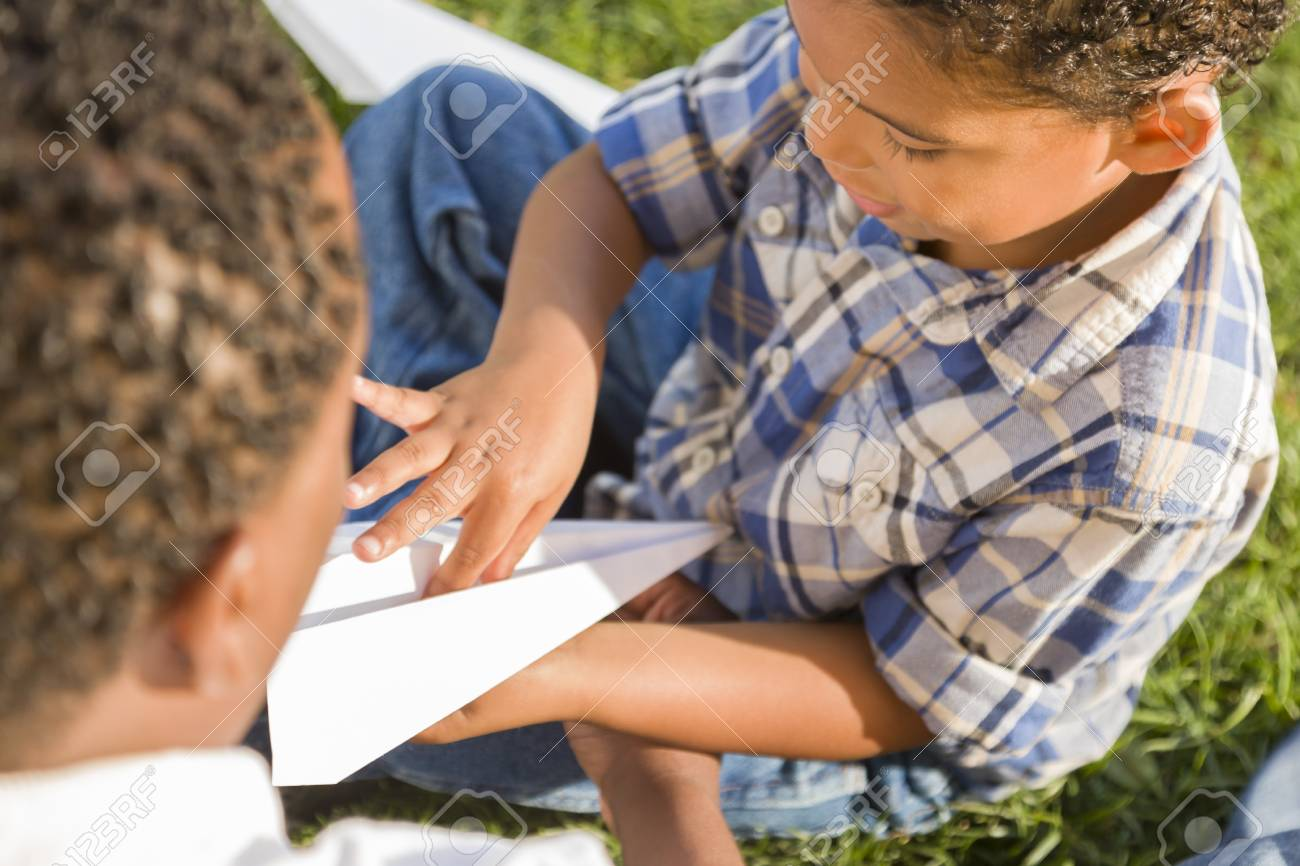 Happy Mixed Race Father and Son Playing with Paper Airplanes in the Park. Stock Photo - 14391244