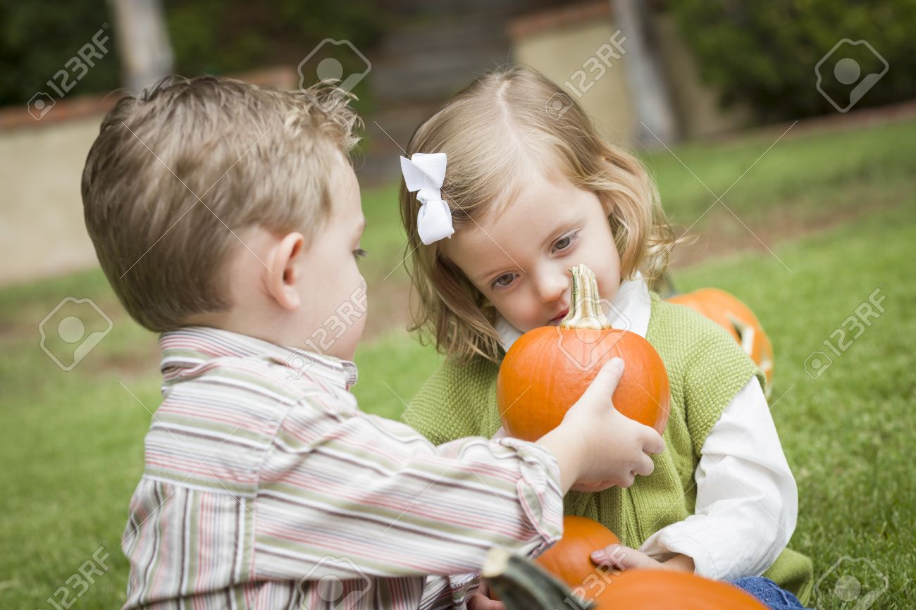 Cute Young Brother And Sister Children Enjoying The Pumpkins Stock