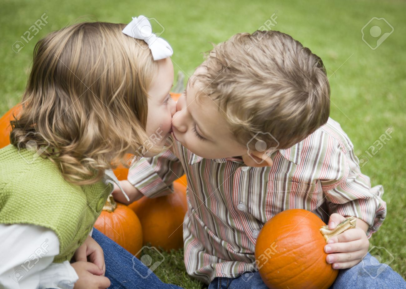 Cute Young Brother And Sister Children Kissing Among The Pumpkins