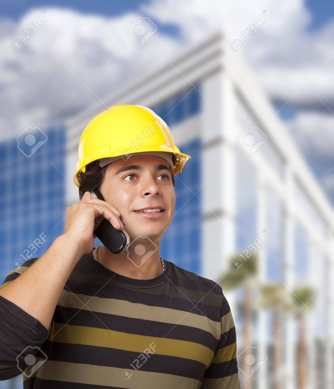 Handsome Hispanic Male Contractor on Cell Phone in Front of Corporate Building. Stock Photo - 16411017