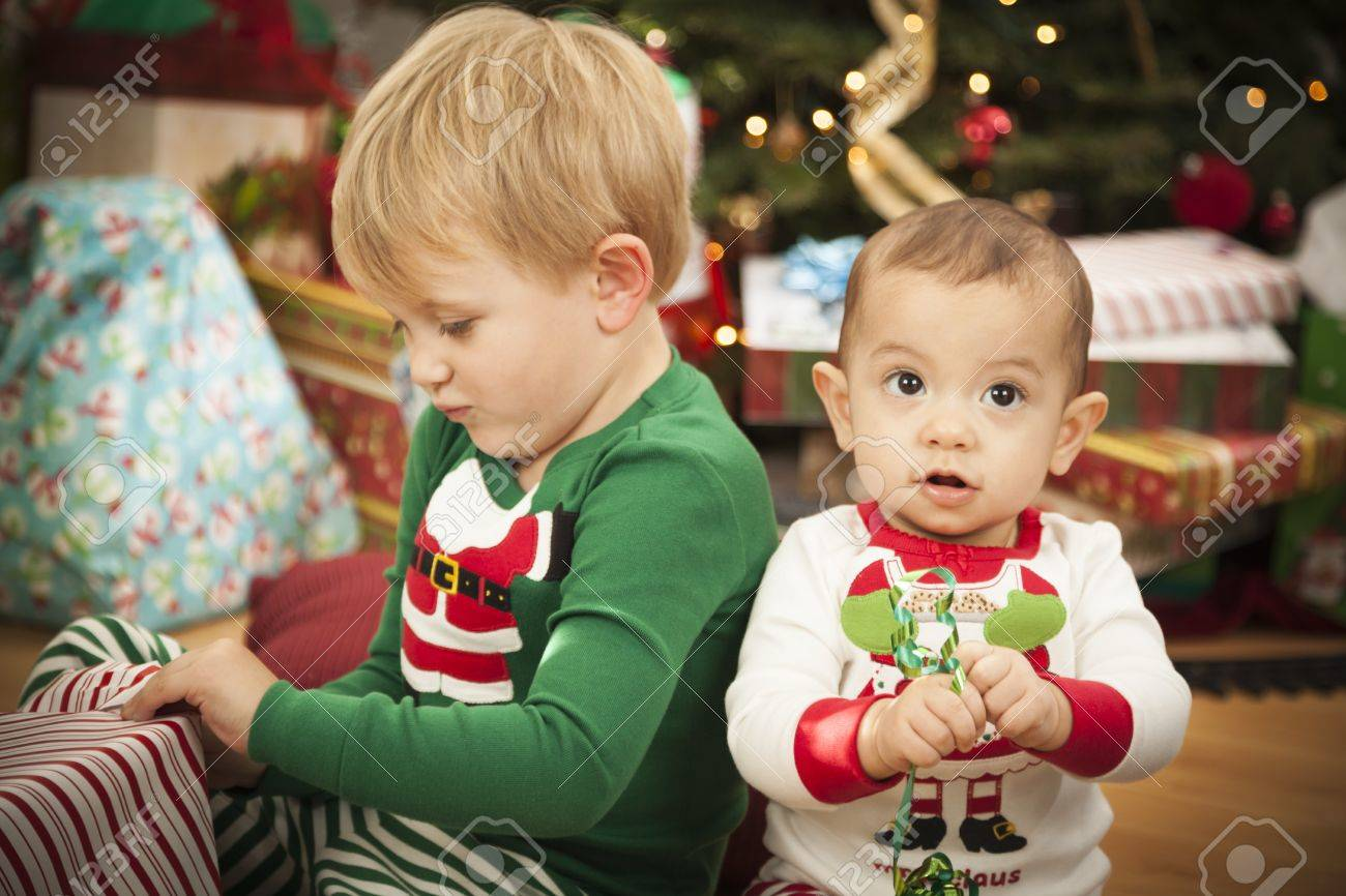 Cute Infant Mixed Race Baby and Young Boy Enjoying Christmas Morning Near The Tree. Stock Photo - 16829976