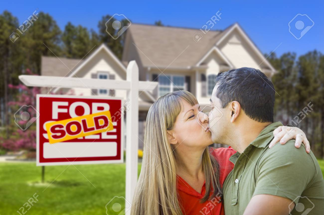 Happy Mixed Race Couple in Front of Sold Home For Sale Real Estate Sign and House Stock Photo - 19223732