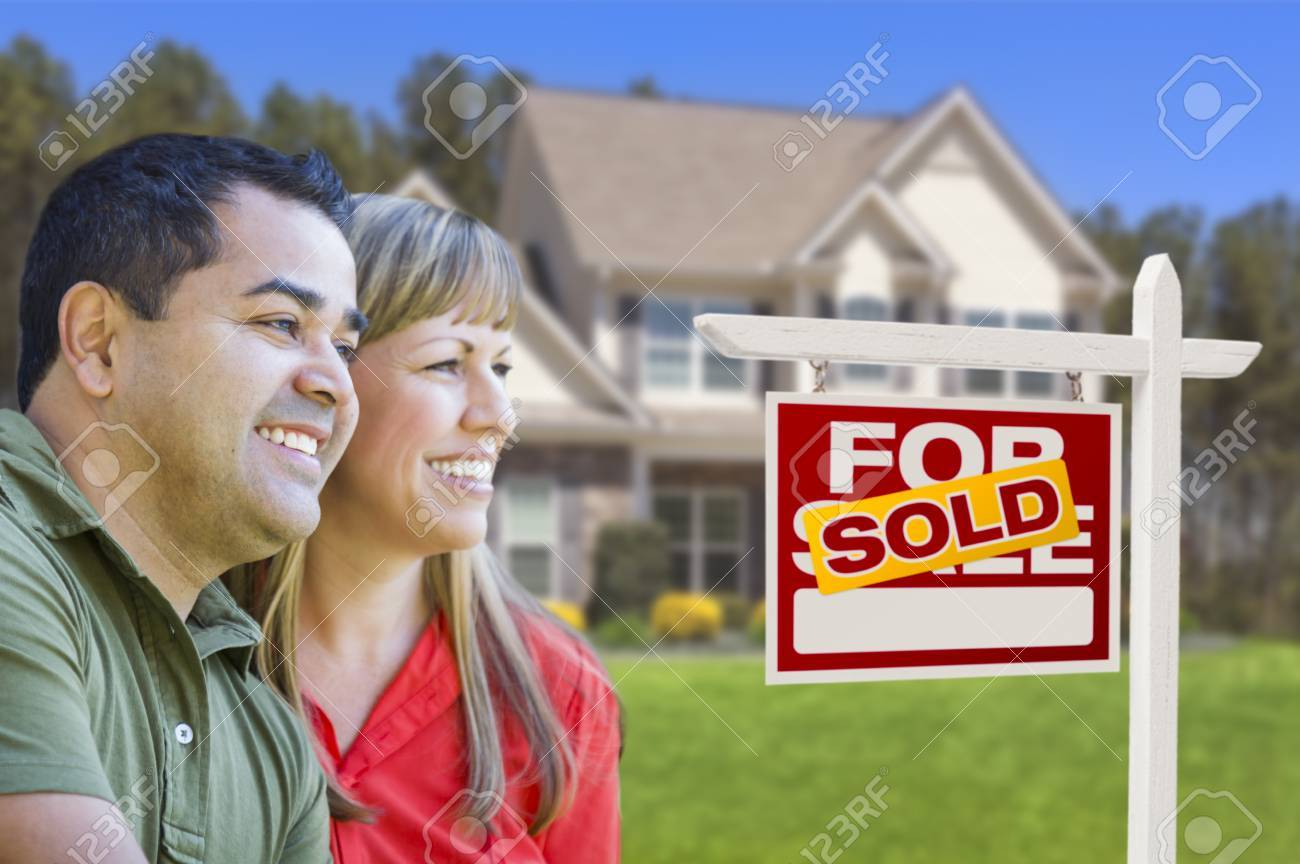 Happy Mixed Race Couple in Front of Sold Home For Sale Real Estate Sign and House. Stock Photo - 19196538