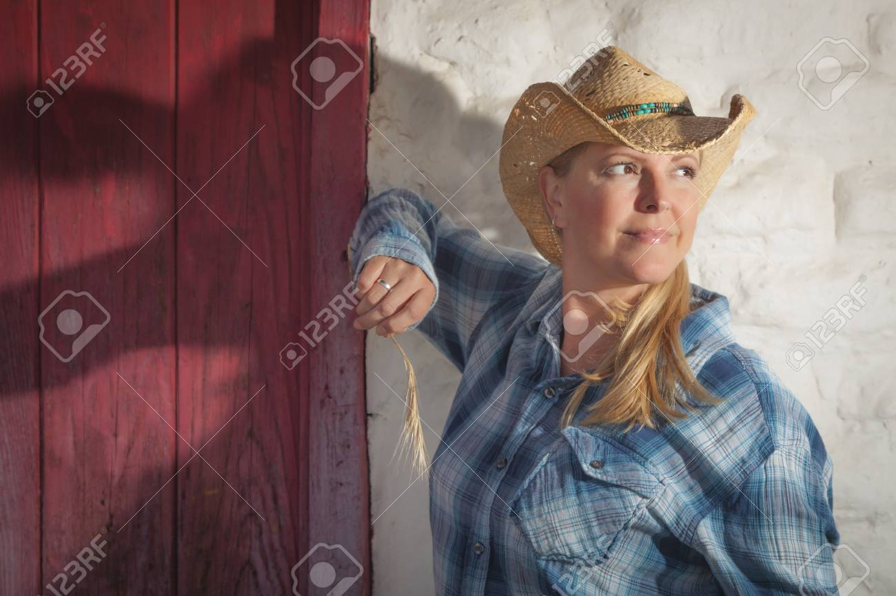 0d6d78085c195 Beautiful Cowgirl Wearing Cowboy Hat Leaning Against Old Adobe Wall and Red  Door. Stock Photo