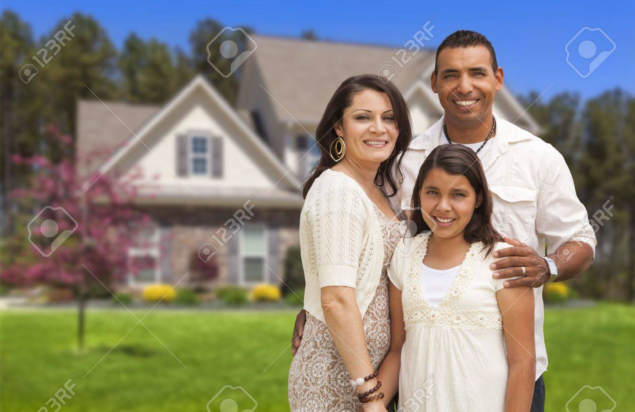 Happy Hispanic Mother, Father and Daughter in Front of Their Home. Stock Photo - 20998978