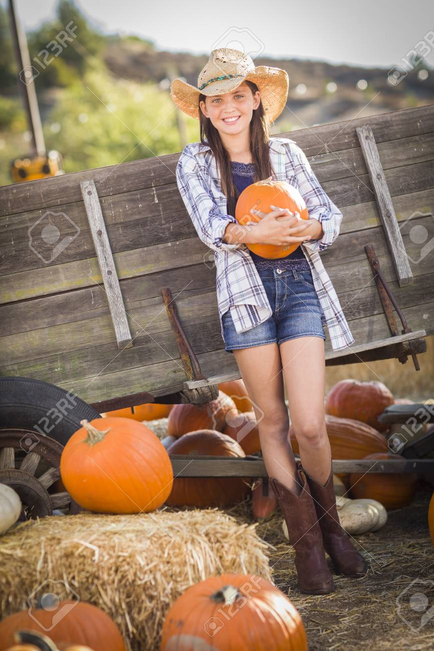 1eafdb6467f Preteen Girl Wearing Cowboy Hat Portrait at the Pumpkin Patch in a Rustic  Setting. Stock