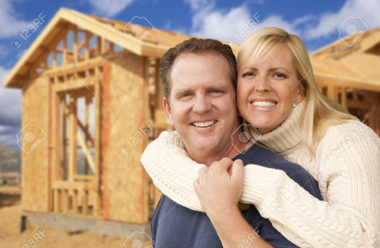 Happy Excited Couple in Front of Their New Home Construction Framing Site. Stock Photo - 24704387
