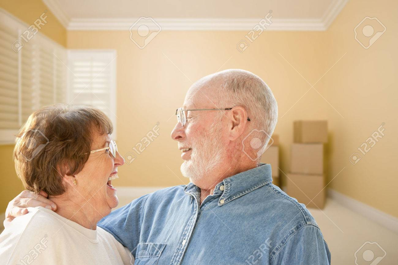 Happy Senior Couple In Room with Moving Boxes on the Floor. Stock Photo - 25107907