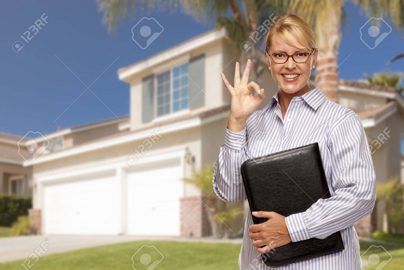 Attractive Businesswoman with Okay Hand Sign In Front of Nice Residential Home. Stock Photo - 28264576