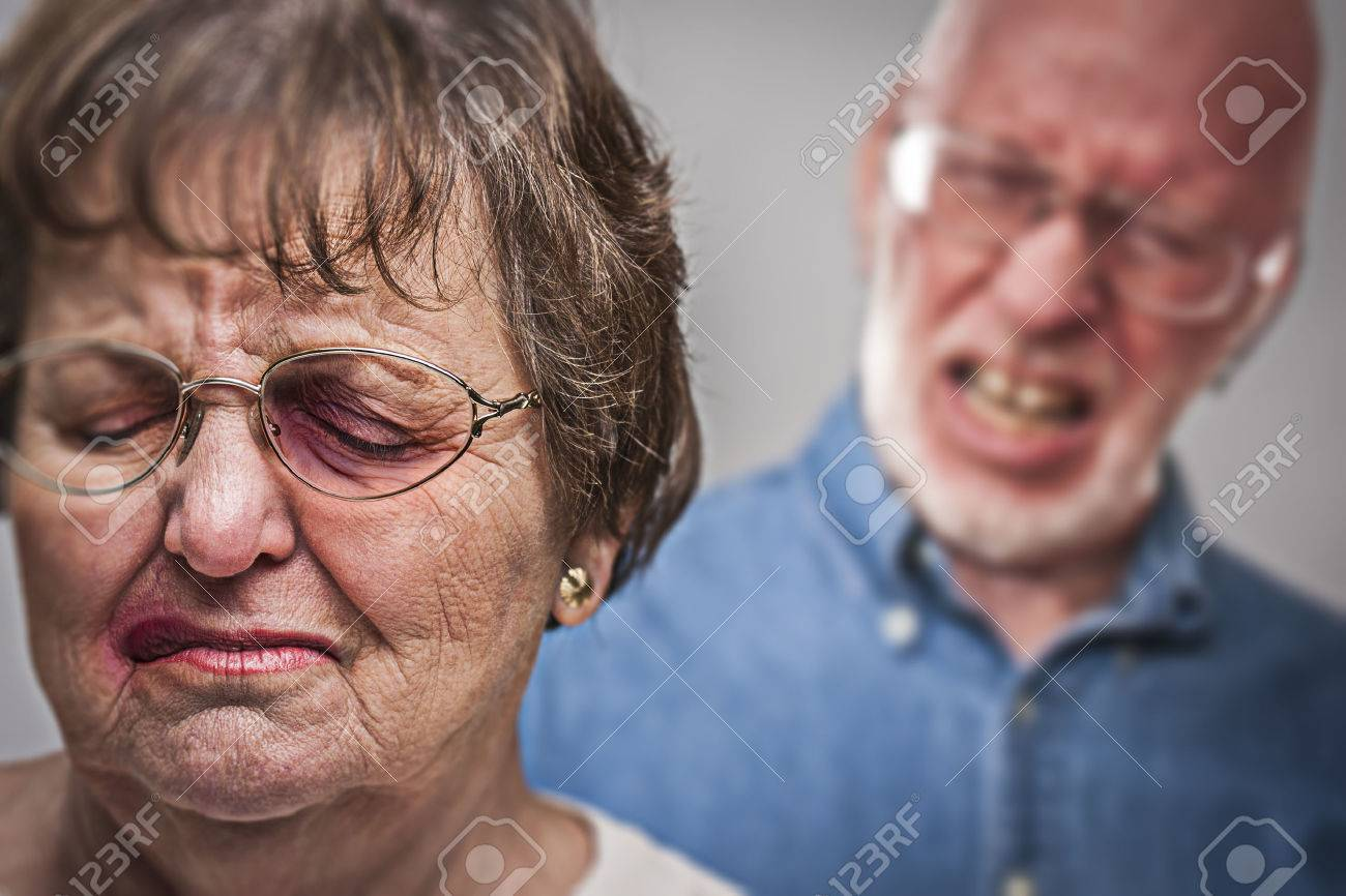 Battered and Scared Woman with Ominous Angry Man Behind. - 32636415