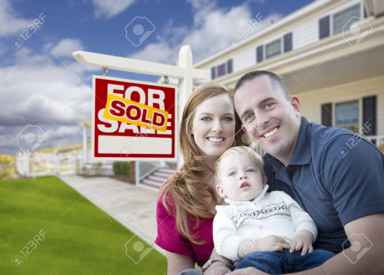 Happy Young Military Family in Front of Sold Real Estate Sign