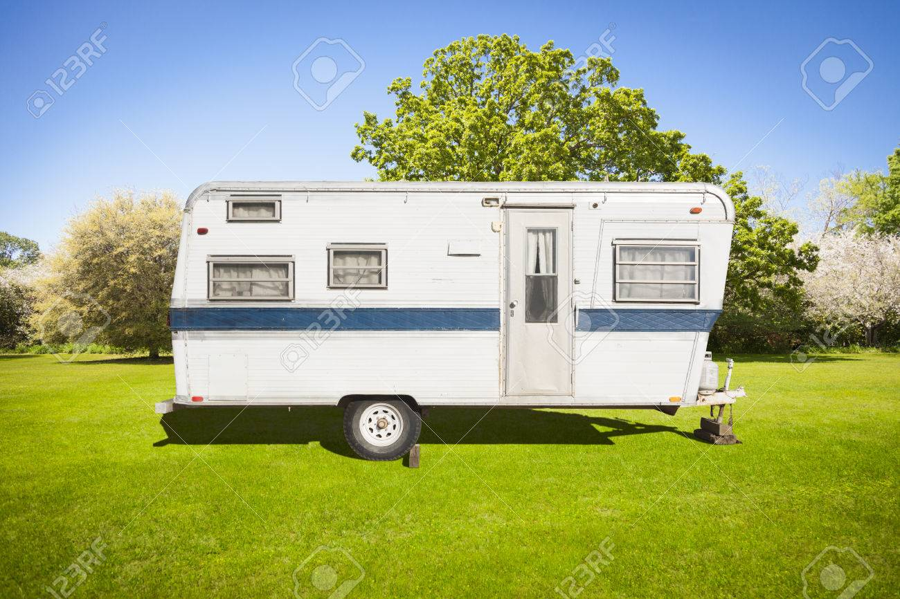 Classic Old Camper Trailer In Grass Field With Beautiful Trees