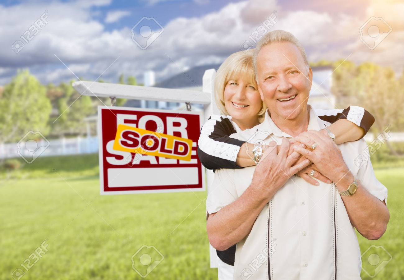 Happy Affectionate Senior Couple Hugging in Front of Sold Real Estate Sign  and House  Stock. Happy Affectionate Senior Couple Hugging In Front Of Sold Real