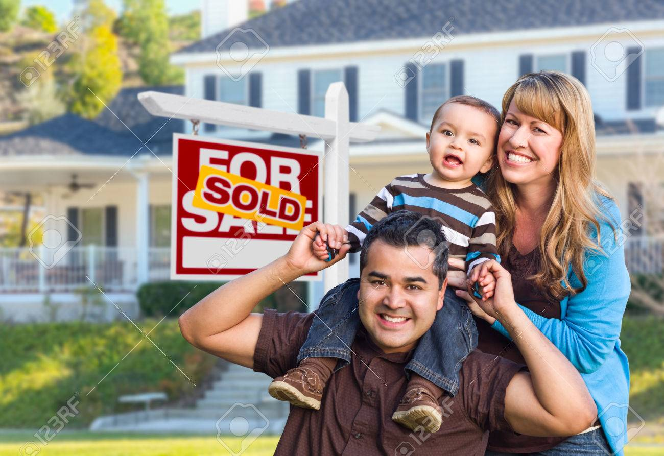 Happy Mixed Race Young Family in Front of Sold Home For Sale Real Estate Sign and House. - 64691334