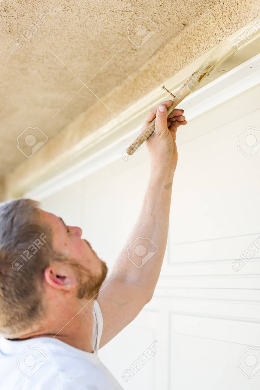 Professional Painter Cutting In With A Brush To Paint Garage.. Stock ...