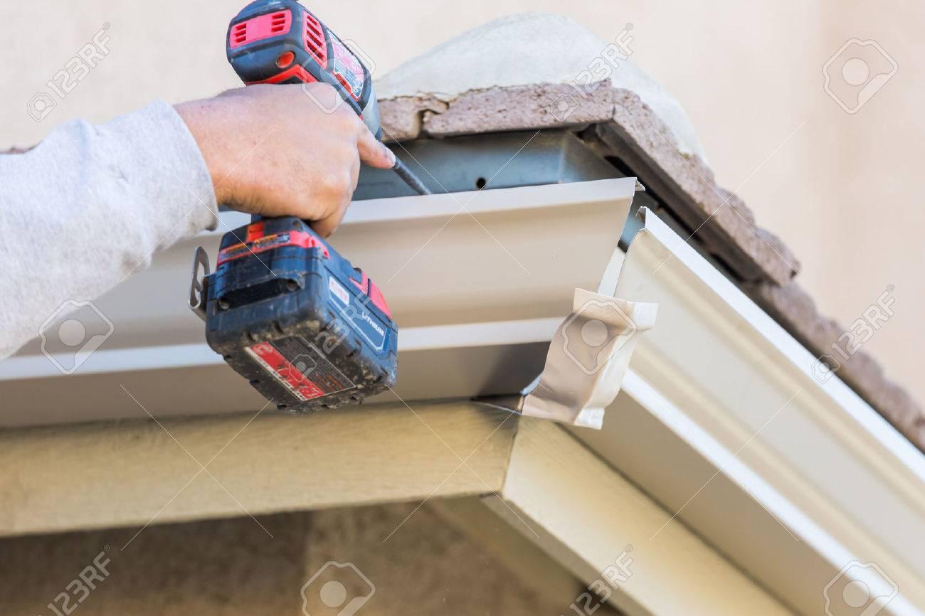 Worker Attaching Aluminum Rain Gutter to Fascia of House. - 72273426