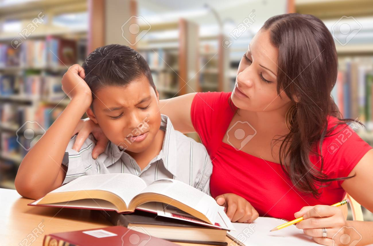 Upset Hispanic Young Boy and Famle Adult Studying At Library. - 106203287