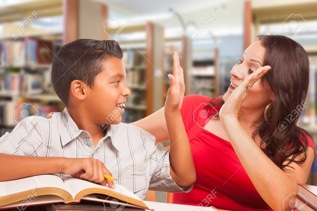 Hispanic Young Boy and Famle Adult High Five Whilte Studying At Library. - 106203297