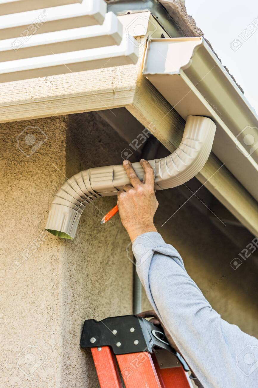Worker Attaching Aluminum Rain Gutter and Down Spout to Fascia of House. - 150324469
