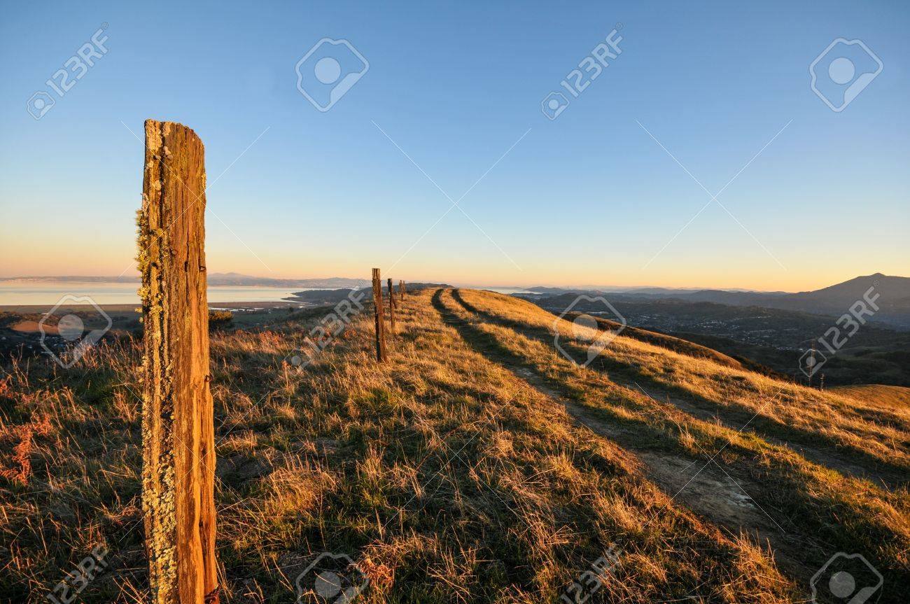 hiking trail on the ridge of a mountain with old wooden fence posts stock photo