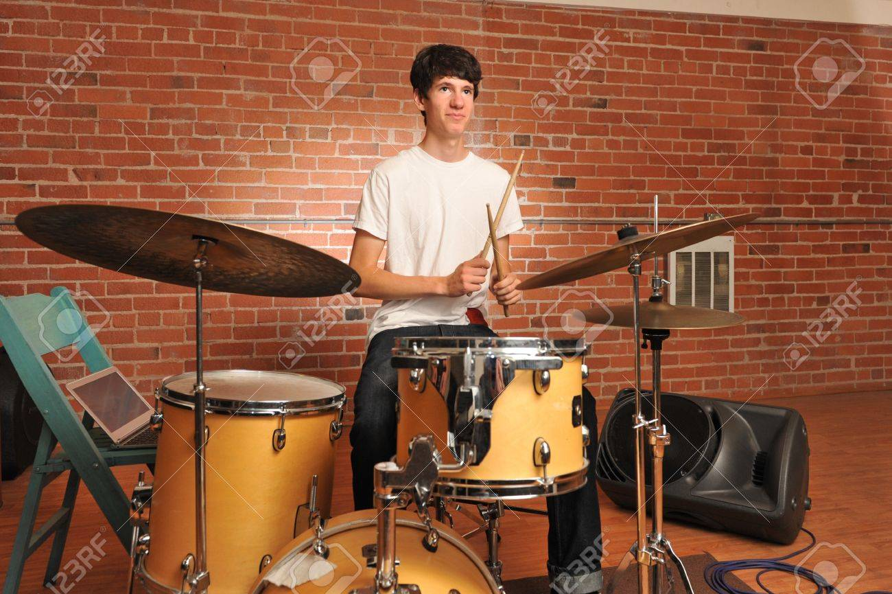 Drummer playing drums in a brick walled studio with computer on chair Stock Photo - 21264675