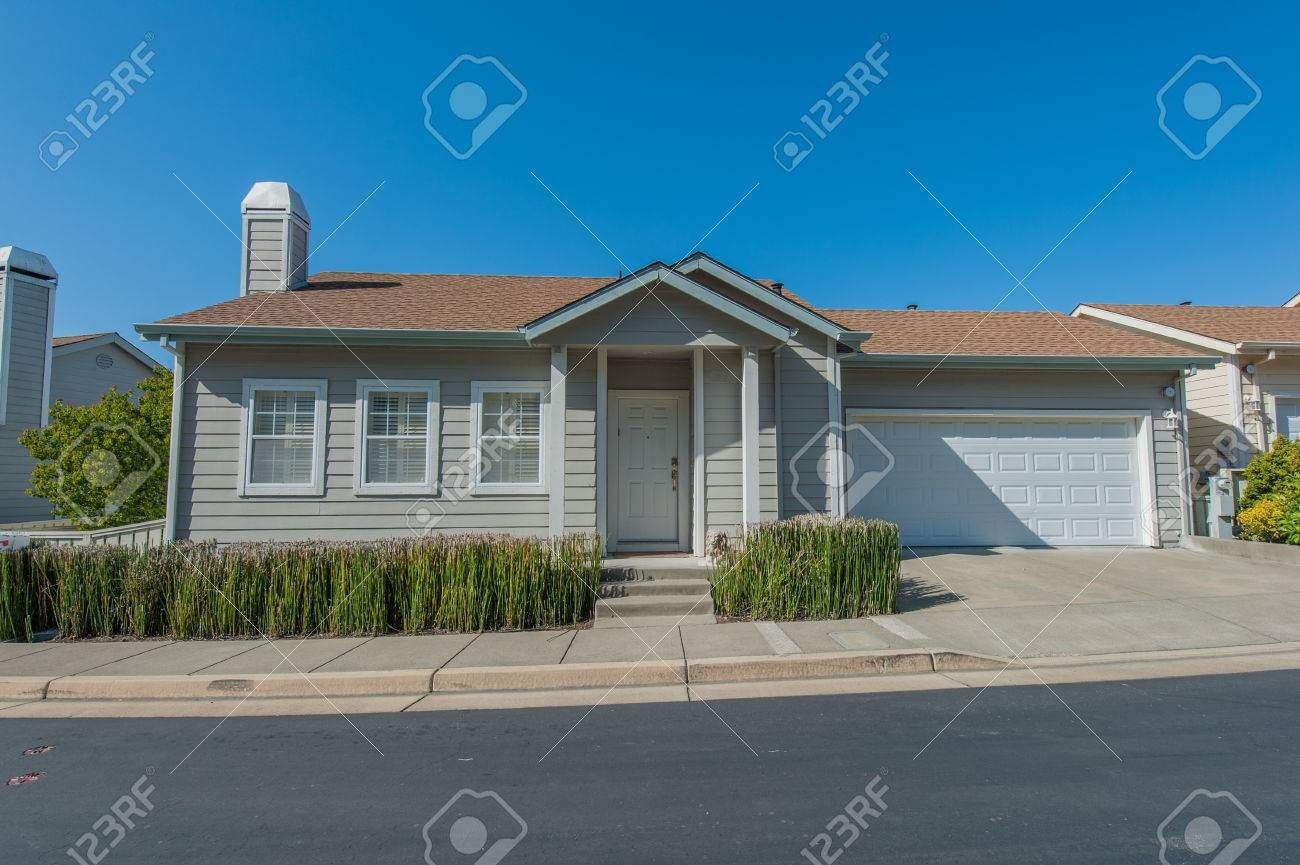 single family house with two levels and a short driveway stock