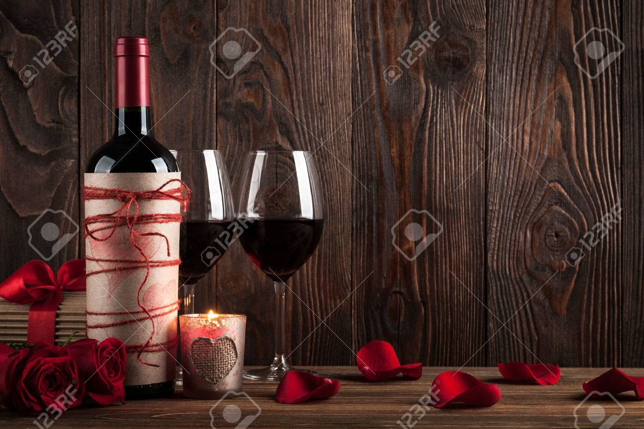 Red wine bottle, two glasses of wine, gift box, candle and red roses on the dark wooden background - 51269732