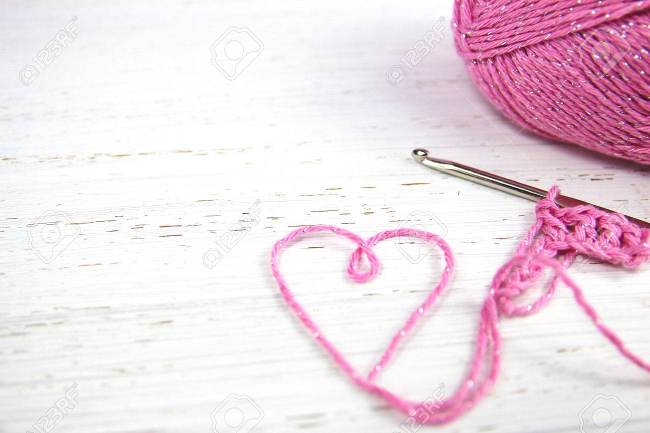 Pink Crochet Background With Yarn Heart On White Rustic Wooden Copy Space Stock Photo