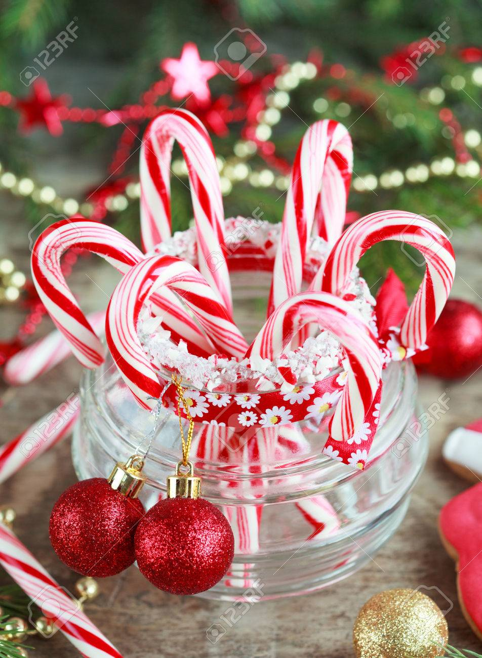 Red Candy Canes In The Glass Jar Between Christmas Decorations