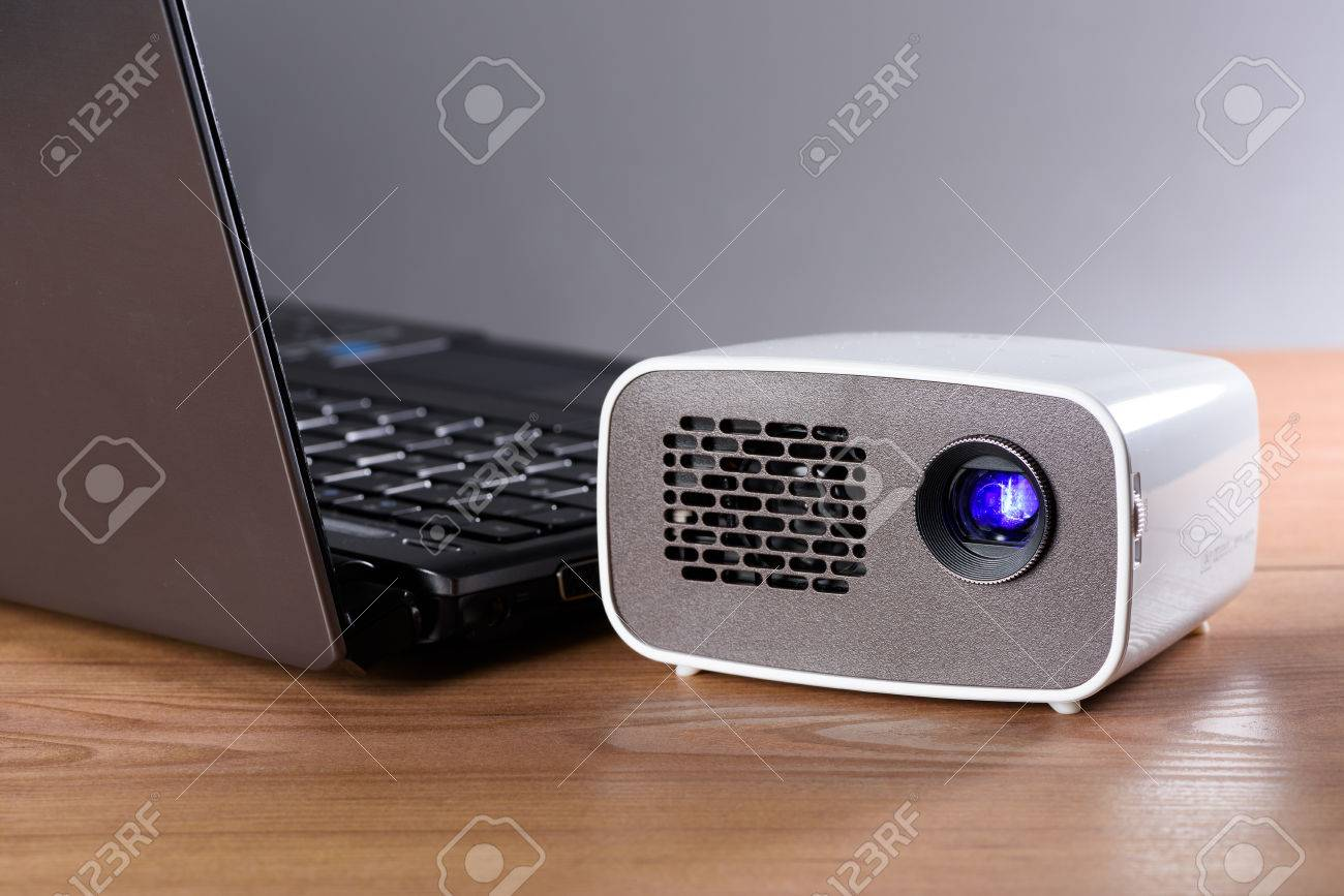 a0c1657e6f1574 Battery operated mini projector with a laptop on a desk. The transfer of  the image