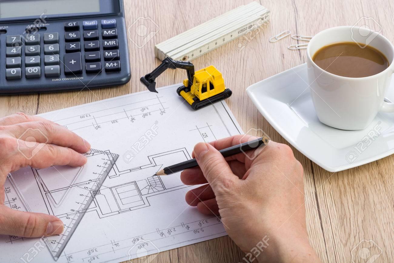 Primer plano de las manos de arquitecto de trabajo en un proyecto calculadora taza de caf y extractor en miniatura en el fondo blueprint fue creado por el malvernweather Images