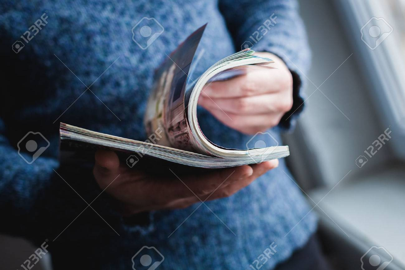 A man looks at a magazine. Press hands. Standard-Bild - 25350631