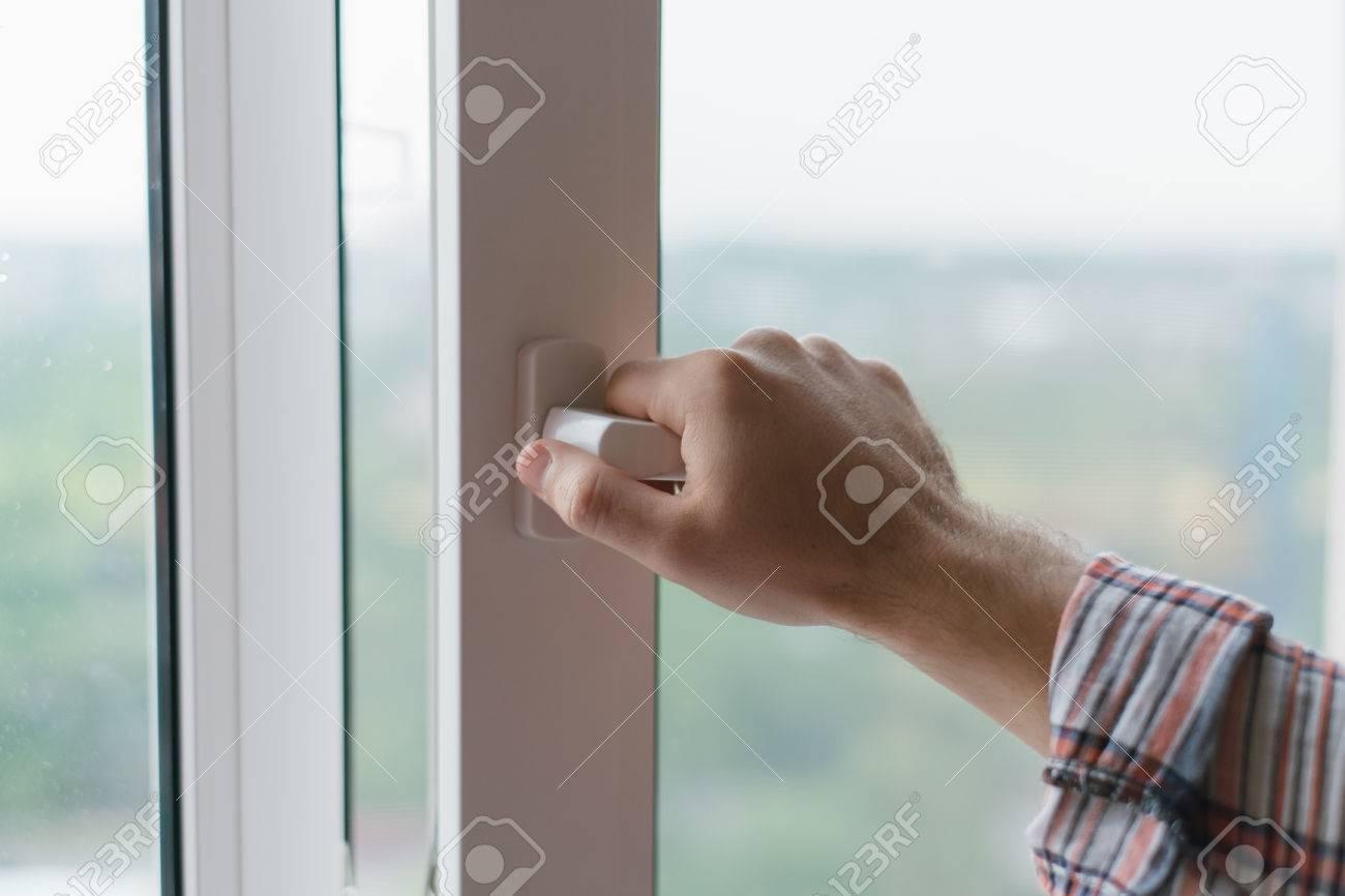 Male hand opens a window - 33710007