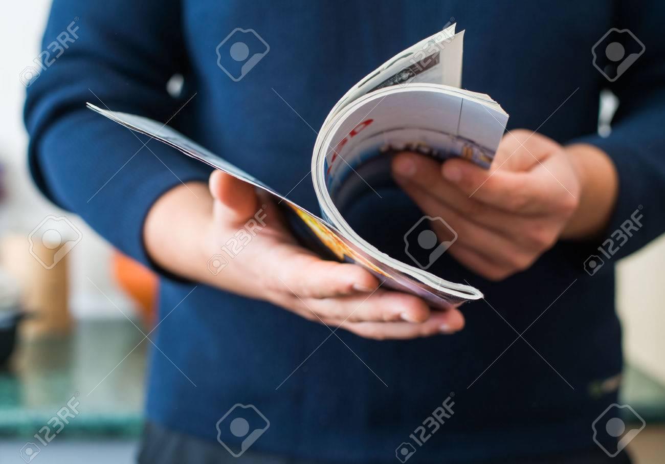 Man reads magazine Standard-Bild - 33715064