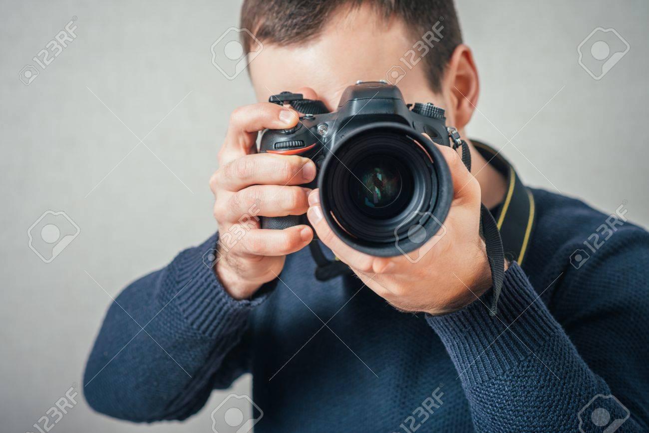 Man photographs on digital camera. On a gray background. - 42327168