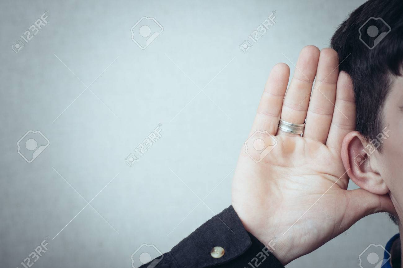 A man with his hand near his ear. Gesture can not hear without listening, talking louder. On a gray background - 42327303