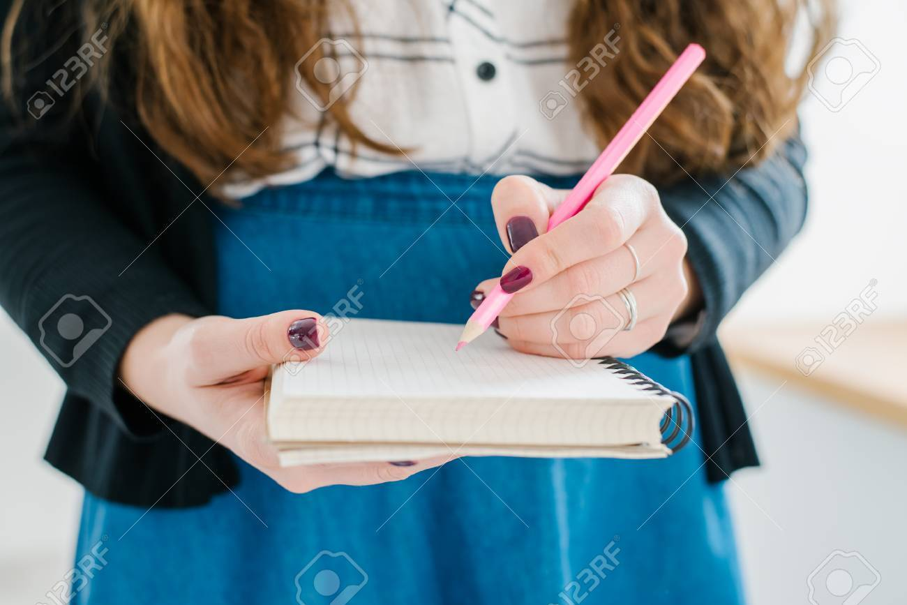 Woman's hand using a pink pencil noting on notepad - 42327526