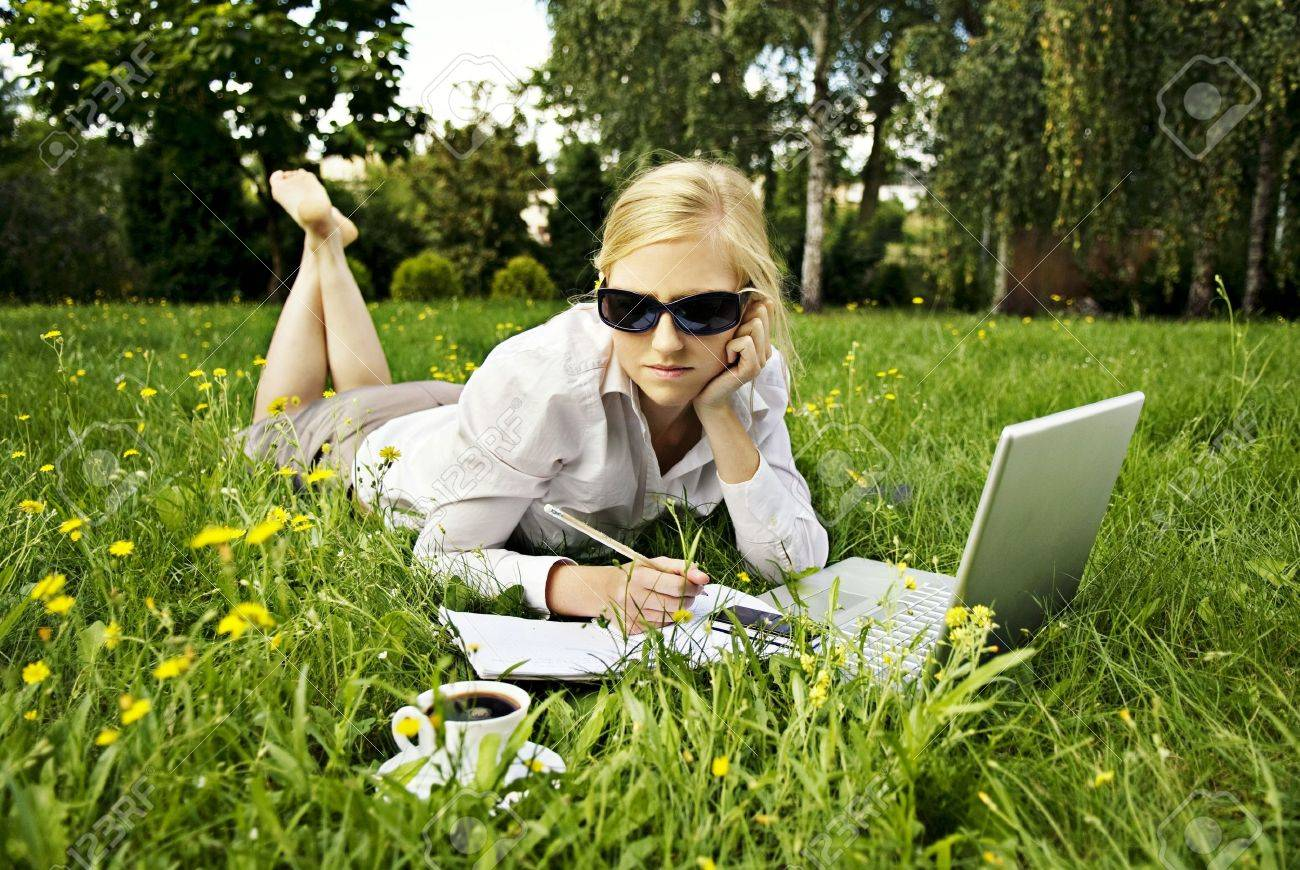 young woman working outside on computer and drinking coffee Stock Photo - 7320280