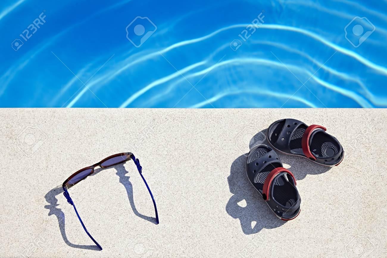 3e6fa998 Gafas de sol y sandalias en la piscina en el día soleado. Copiar el espacio.