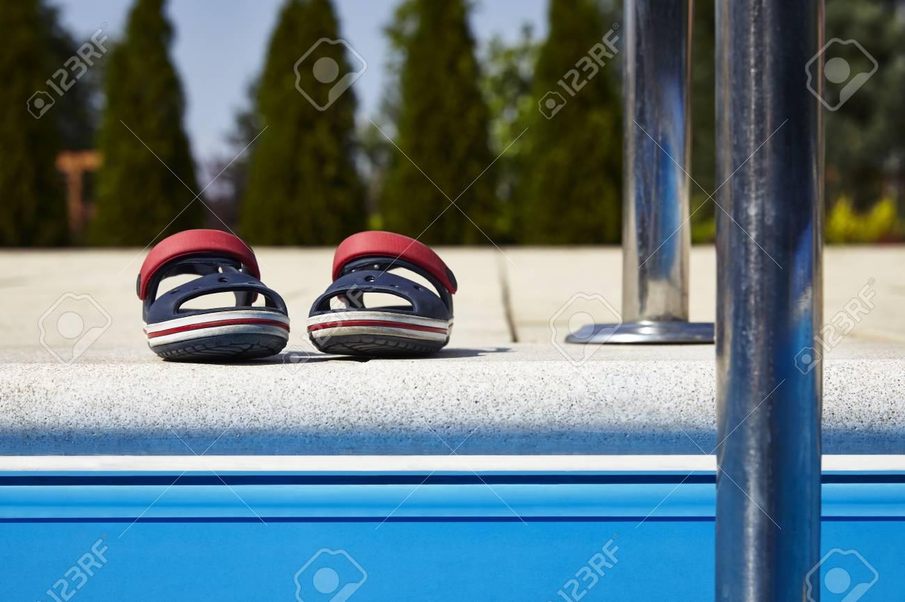 0345f38e Par de sandalias de bebé en el borde de la piscina en el día soleado.