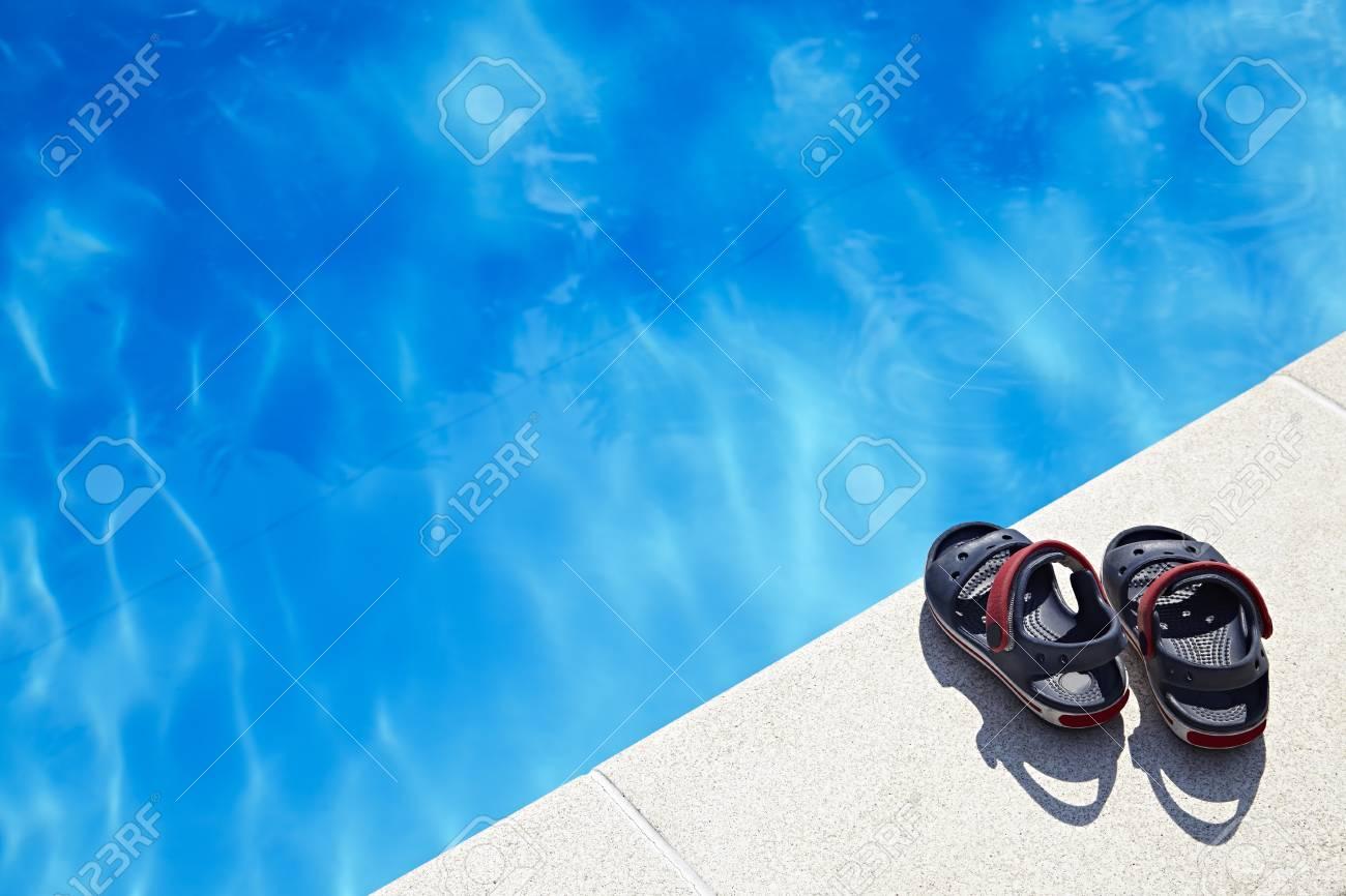 3d6aad9f Par de sandalias de bebé en la piscina en el día soleado. Copiar el espacio.