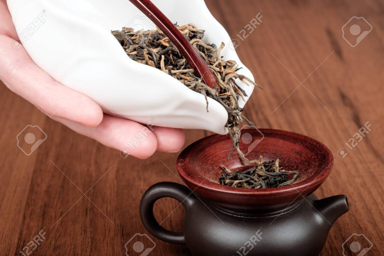 Faire du thé noir chinois dans une petite théière en porcelaine