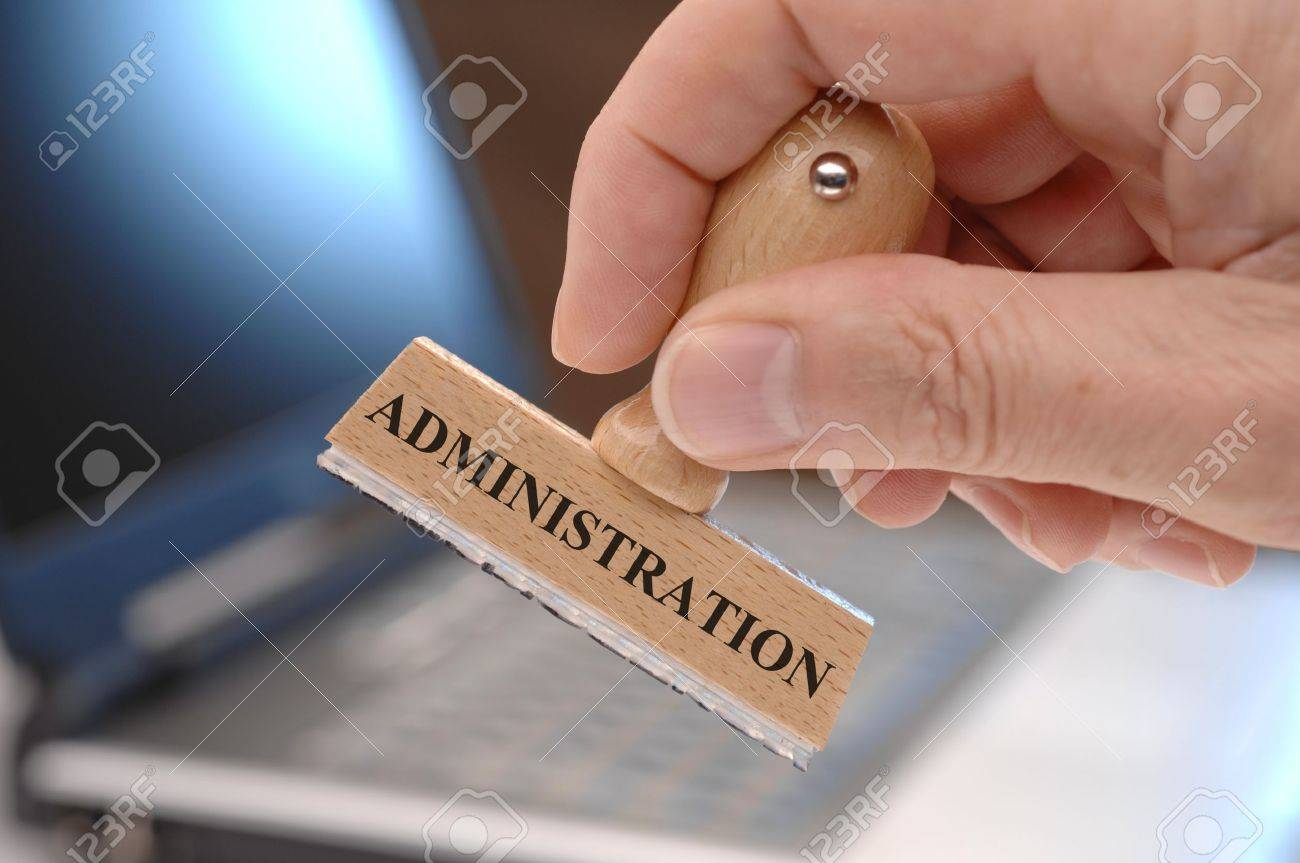 rubber stamp in hand marked with administration - 18965411