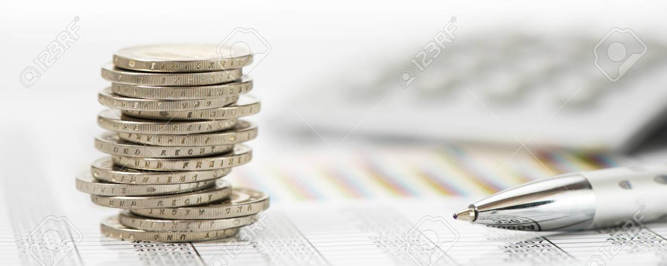 stacked coins over data of stock market with calculator - 80698492