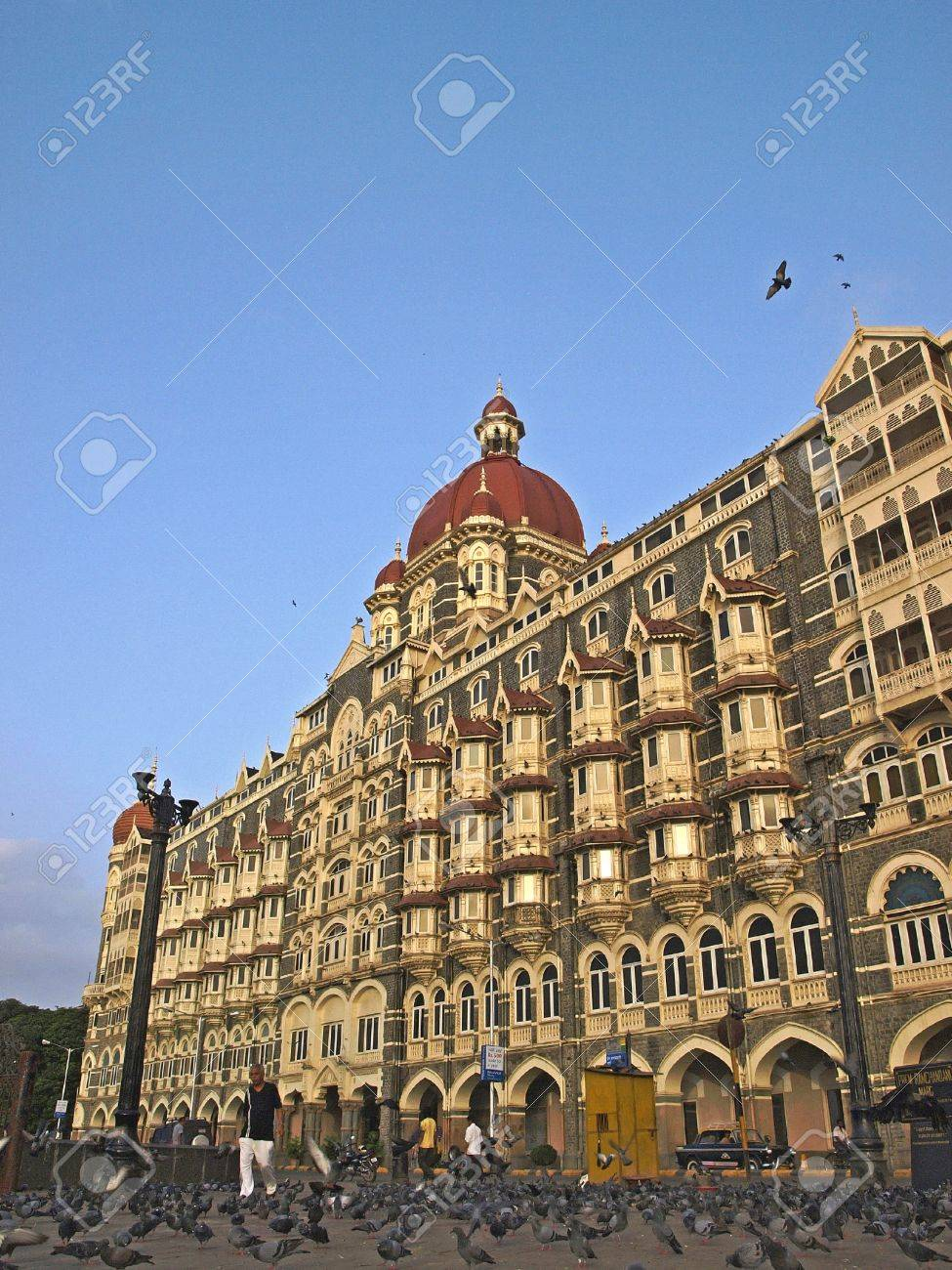 MUMBAI, INDIA - JULY 18, 2008: Crowding of pigeons are stepping in front of the Taj Hotel, a renown hotel that was designed by Indian architect; Sitaram Khanderao Vaidya in Mumbai, India.       Stock Photo - 17227991