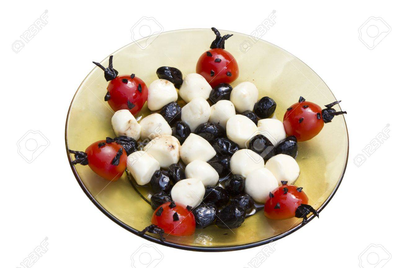 Tasty decorated plate with black olives, ladybug tomatoes ...