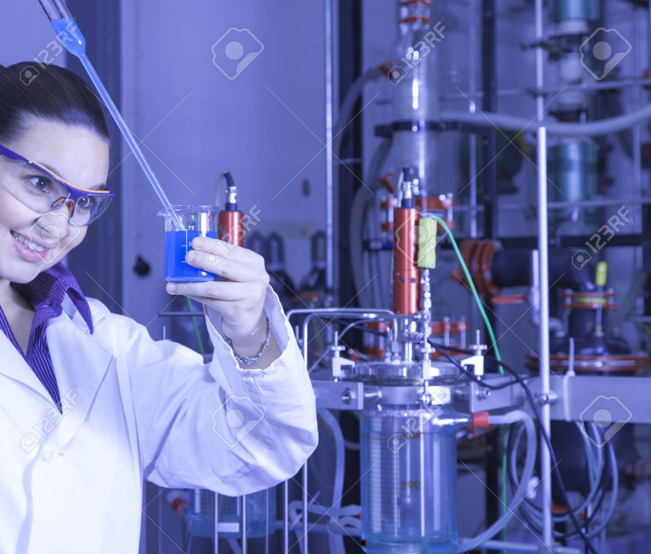 Closeup of a cute female researcher holding test beaker and tube with chemicals, while carrying out some experiments in a laboratory, focus on liquid in test tube, blue color toned image Stock Photo - 16119170