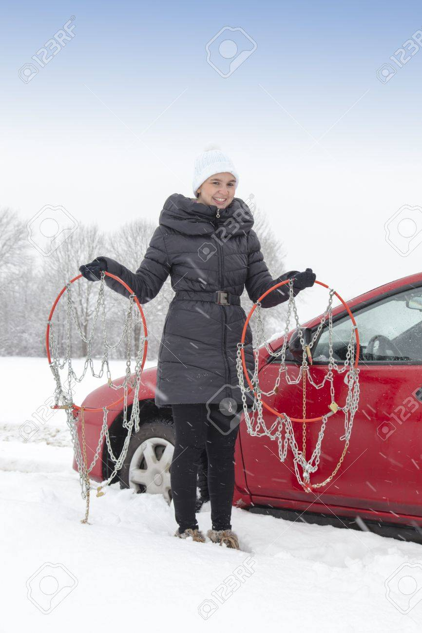 Cute female driver holding tyre chains on snowy winter day and waiting for help Stock Photo - 17381661