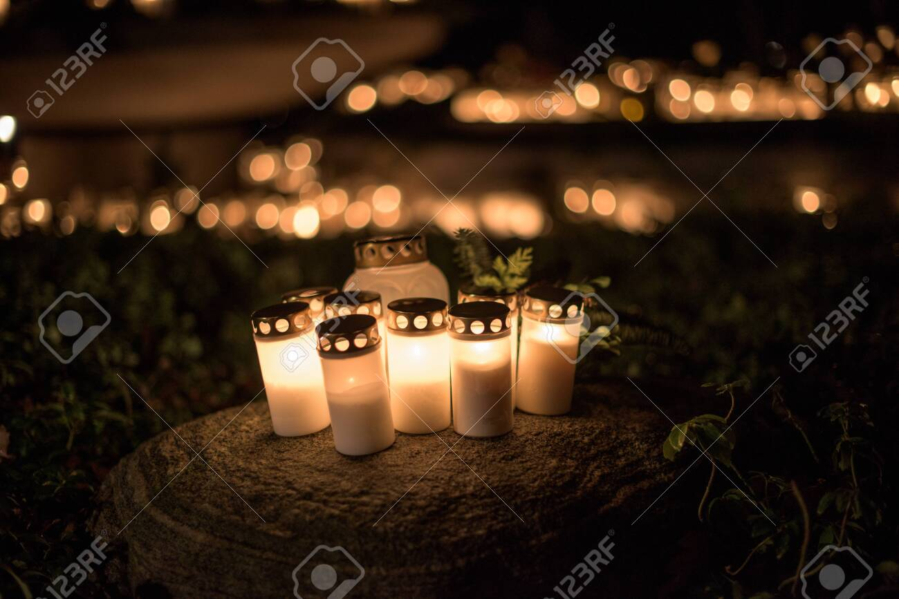 lit candles on a stone at a graveyard - 122131097